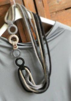 Collana in maglia di lana nei toni del beige grigio e nero.