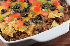 Mexican Casserole   1lb ground beef   1 (1 ¼ ounce) package taco seasoning  1 (15 ounce) can refried beans  2 cups Colby jack cheese  1 cup salsa  1 (2 1/3 ounce) can sliced black olives (drained)  1 tomato (chopped)  2 cups corn chips (crushed)