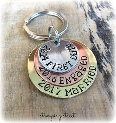 Love Story Keyring - New for Valentines Day. The three metal stacker keyring is one of our best sellers. It boasts three different metals being brass, copper and aluminium. Slightly curved to add interest and reflect light and polished to perfection, the discs are attached by a split ring through a hole at the top, allowing each disc the freedom to move. Each disc will be stamped by hand, with the wording or dates of your choice. You can anything you like on it, as long as it fits! In one…