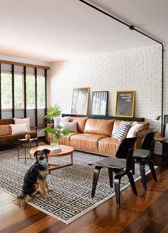 Decoração de apartamento. Parede de tijolinho branco, quadro, sofá marrom, tapete preto e branco, mesa de centro com adornos, cadeira preta.  #casadevalentina #decoracao #decor #details