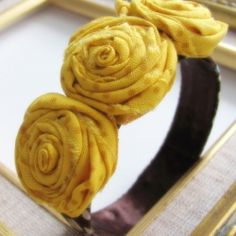 I'm seeing rolled fabric roses and other fabric flowers all over the place lately. Make yourself a bracelet to show them off.