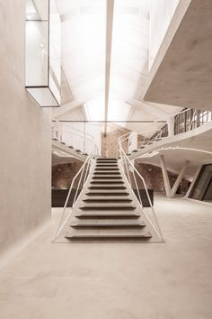 Smartvoll adds sculptural concrete staircase to loft apartment in old Salzburg tank station