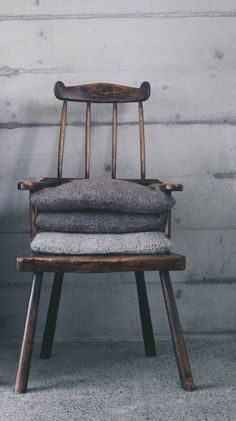 The Welsh House - Bryncyn - review and blog at meandorla. Wooden chair, woolen blankets and concrete walls. Minimalist and modern meets old interiors.