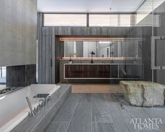 A mix of natural elements—wood-like tile floors and custom vanities fabricated by George Peker's Addhouse topped with Walker Zanger's White Macaubus—shine alongside man-made materials in earthy tones, such as the chevron tile wrapping the fireplace and planks of porcelain tiles surrounding the sunken bath and in the shower. Vanity Countertop, Walker Zanger Tile, Traditional Architecture, Show Home, Custom Vanity, Chevron Tile, Wood Like Tile, Contemporary Interior, Sunken Bath
