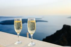 Two glasses of sparkling wine on a ledge overlooking blue sea and the horizon…