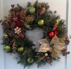 Artificial evergreen wreath decorated with bronze foliage, poinsettias, shatterproof ornaments, snowflakes and an owl.