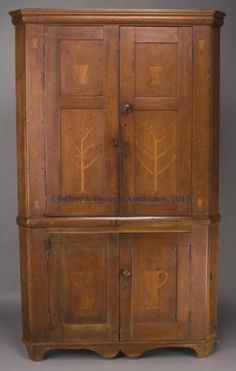 "AMERICAN FOLK ART INLAID WALNUT CORNER CUPBOARD, in one piece, applied cornice above two double-panel doors, an applied waist molding, & two lower single-panel doors, raised on cut-out feet flanking a double-scallop skirt. The upper doors inlaid with a cross-hatched basket in each upper panel & a naive tree in each lower panel…Probably Western Virginia, Kentucky or Ohio. First half 19th century. 85"" H, 50 1/2"" W, 19 1/2"" D."