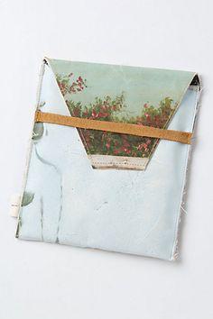 capa para i pad com reaproveitamento de telas pintadas, forrado com algodão e fechamneto de couro