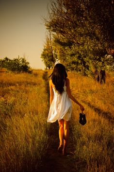 Girl Walking Away | Barefoot girl in white dress with shoes in hand is on the field.