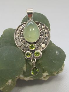 "Handmade polished cabachon Prehnite and sterling silver gemstone pendant, paired with 4 faceted Peridot gemstones including pear-shaped dangle, all set in 925-hallmarked sterling silver. Length: 2"" in"