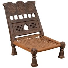 An old Indian rustic wooden low chair from the early 20th century, with handwoven rope seat and carved motifs. Charming our eyes with its rustic appearance, this low seat wooden chair features a short slanted back, adorned with three rosettes hand carved in low-relief within medallions, resting above a series of petite hourglass-shaped motifs followed by pierced accents. The rectangular seat, made of handwoven rope, is low and rests on four short feet, the front ones being baluster-shaped…