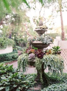 Fill an old, antique fountain with stunning succulents and wildflowers for a gorgeous display. This looks so romantic and luxe! Image via Style Me Pretty. #antiquegardenfountains