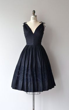 Exceptionally well-made 1950s dress in black cotton with gathered shoulders detailed with tiny tied bows, deep neckline, plunging back, fitted waist,