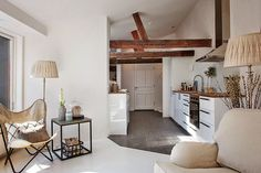 A tiny rustic farmhouse style white Swedish apartment with inspiring decor including wood beams and white painted floors. One of my all-time favorite Swedish apartments!