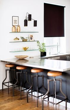 In the New York loft of stylist Rita Hazan, vintage industrial stools are paired with a chic French three-arm sconce and simply-styled floating glass shelves, giving the space plenty of...