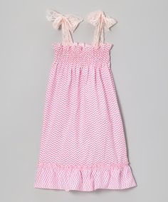 Feminine and fun, this darling dress shows off a pink zigzag pattern and ruffle trim. A shirred bodice and adjustable lace straps keep it comfy through all of a little one's skips and twirls.