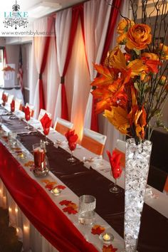 Red and white and orange fall wedding backdrop and head table with lights. Fall wedding leaves and branch centerpieces, tall wedding centerpieces