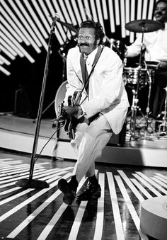 """Chuck Berry doing the """"Duck Walk' with a Gibson 33-something archtop guitar"""