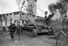 """https://flic.kr/p/ejLWdU   1945, Russie, Des soldats russes au combat passent près d'un """"SdKfz 161 Panzerkampfwagen IV (PzKpfW IV)"""", ou """"Panzer IV"""" en feu"""