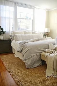 Light & bright master bedroom - a gray, white, & navy room. Windows as a headboard, DIY dresser dark gray nightstands, Rugs USA natural fiber rug, & a DIY TV console too!
