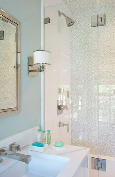 Laura Tutun Interiors Bathroom Interior Design Portfolio. Contemporary bath with classic lighting, beautiful tiled shower, and cool blue walls