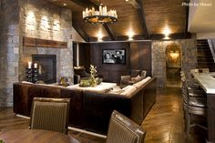 Basements do not get more traditional than this with the stone fireplace and wooden bar above, dark hardwood floors, a brown leather couch, dark upholstered bar stools and stone and wood walls all around. See other amazing basements remodels. #traditional #stone