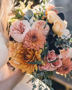 Dusty coral and pink and orange blooms make this a beautiful late summer or autumn/fall wedding bouquet