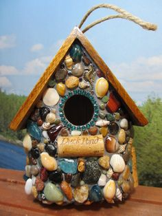 MOSAIC BIRDHOUSE: I think this would be fairly easy to make myself. A few shells, some colored rocks and 7 pieces of appropriately measured and cut wood and voila!