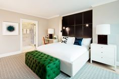 Emerald tufted bench at the end of neutral bed with navy pillow and leather statement wall