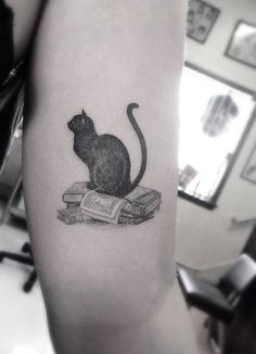 Fine line style black cat on top of a bunch of... - Little Tattoos for Men and Women