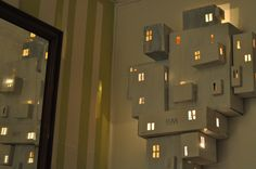 Kartonkisten aneinandergeklebt, dahinter Leuchtkette