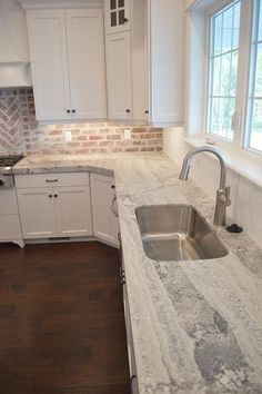 Amazing kitchen features a white shaker cabinets paired with gray quartzite countertops fitted with a curved stainless steel sink and a white subway tiled backsplash. - August 04 2019 at Kitchen Redo, New Kitchen, Kitchen Remodel, Kitchen With Brick, Kitchen Ideas, Kitchen Layout, Armoires Shaker, Look Wallpaper, White Subway Tile Backsplash