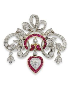An Edwardian ruby and diamond brooch pendant, of diamond bow and ribbon design with calibre-cut rubies and heart shaped diamond drop, circa 1910.