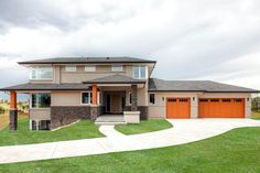 Three level design with walk out lower level. Exterior orange color on garage on pillars creates contrast on this custom home design.