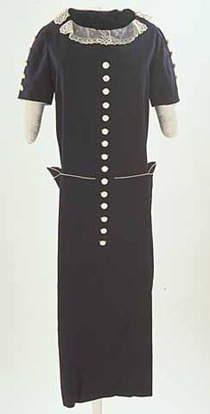 Wool gabardine dress ensemble, ca. 1924. Dark blue wool gabardine chemise with short set-in sleeves, linen cuffs with lace trim, lace collar, pockets with flaps, half belt in back, and waist detail trimmed with white grosgrain. Center front decorative button tab has mother of pearl shank buttons and buttonholes trimmed with white grosgrain. Mother of pearl buttons also decorate sleeves.  ID Number: 62.1.6.B  Minnesota Historical Society