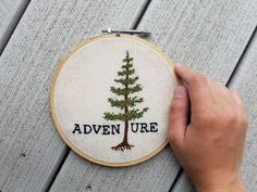 ADVEN(T)URE is out there. This lovely piece features a pine tree as the t in adventure as inspired by John Muirs quote - The clearest way into the universe is through a forest wilderness. Hand embroidered by me, Megan Jane, this piece is framed in a 6 vintage embroidery hoop and ready to display.