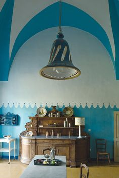 Lucia Guarini designed the blue wall pattern to enliven a supply room, and made the ceramic chandelier. (Photo: Ricardo Labougle)
