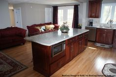 The built-in microwave under the island stood out in this remodeled kitchen. Kitchen shows off an arched neck faucet, steel kitchen sink, beautiful hardwood floors and red sofas for some extra seating. See how you could update this kitchen by clicking on the Pin.