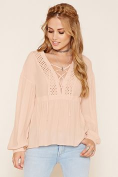 A semi-sheer woven top featuring a loose silhouette, eyelet crochet  paneling, V-neckline with self-tie laces, and cuffed long sleeves.