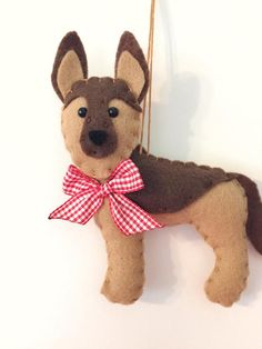 This sweet ornament makes a great gift for anyone who loves or has a German Shepherd! He is designed and handmade by me. He is made of soft felt and has a red gingham bow. He is about 5 inches long. Find more cute felt critters here Felt Ornaments Patterns, Dog Ornaments, Felt Christmas Ornaments, How To Make Ornaments, Christmas Crafts, Dog Crafts, Felt Crafts, Needle Felted Animals, Felt Animals