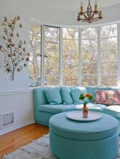 A lovely curved turquoise sectional sofa is nestled into a large bow window with beautiful views in this Los Angeles apartment (via Samer...