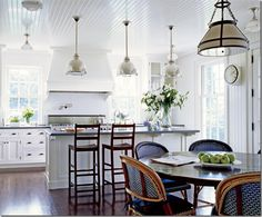 This kitchen is a little too white for my taste, but those lights over the island are so pretty...also the touches of black in the cabinet hardware.