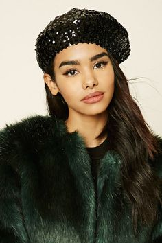 A knit beret featuring an allover sequined design and elasticized brim.