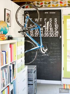 Graphic elements like an oversize calendar and chalkboard are both practical and decorative. Open rafters offer storage spots for bright plastic tubs, while a hint of the garage's original use comes through in the bike hook. If your space is intended for multiple users, place furniture in strategic spots to create different work zones.