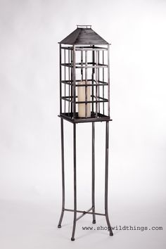 """This awesome candle lantern has it's own stand so it doesn't have to be placed on a tabletop for elevation. Fill it with candles, floral, river rocks, moss….8-1/2"""" x 8-1/2"""" x 49""""Tall The finish is done"""