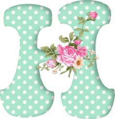 An alphabet of pale green letters with white polka dots and a spray of pink roses.