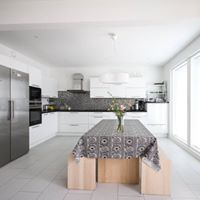 Keittiön lattia on isoa laminaattia laatta kuosilla. Kyseinen lattia on todella helppoa ja nopeaa asentaa. Lisäksi materiaali on kulutusta kestävää sekä helposti puhdistettavaa. Kuvan pöytä on puusepänliike Hannes Oy:n käsityönä tekemä.