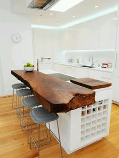 wood slab as the counter top of the island in the kitchen