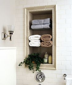Love the use of a frame or molding to look like a frame around shelves in a bathroom. It gives storage pizazz!