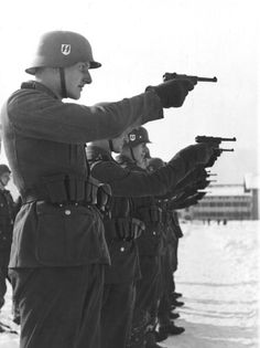 Waffen-SS grenadiers are seen at target practice with their P.08 Luger pistols in winter gear on a snow-covered range. Note that their holsters are on the left side of the belt so that the pistols could be cross-drawn.